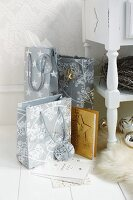 Gift bags with Christmas motifs on white wooden floor