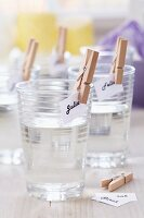 Name tags attached to drinking glasses with clothes pegs