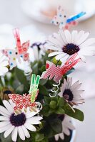 Paper butterflies attached to flowers with clothes pegs