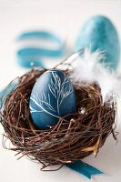 An egg painted with natural dye (red cabbage) for Easter, in an Easter nest