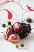 Three Easter eggs colored with natural dyes (red beet)