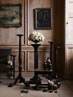 Nostaslgic room with paneled wall, wooden chair, carved wooden pedestals, flowers, wooden tables and old paintings