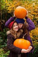 Zwei Mädchen halten orangefarbene Riesenkürbisse im Garten