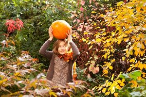Mädchen balanciert einen orangefarben Riesenkürbis auf dem Kopf
