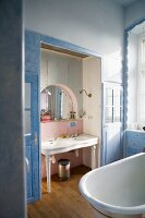 A view into a bathroom with a free-standing bathtub and a washstand