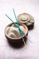 Fine sand in ceramic bowls, incense sticks and a fossil