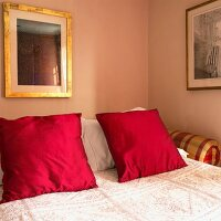 Double bed with red pillows and bedspread (close up)