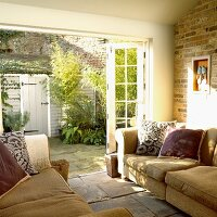 Living room with sectional sofas and open doors into a courtyard filled with green plants