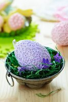 Easter egg decorated with lace doilies and campanula flowers in metal cake mould