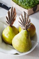 Pears decorated with newspaper leaves
