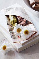 Guest favour of folded newspaper pocket filled with sweets and flowers