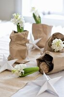 White hyacinths in crumpled bags of brown packing paper as festive table decoration
