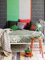 Tagesbett mit nostalgischem Bettgestell und bunten, selbstgenähten Zierkissen vor Wand mit breitem Streifenmuster