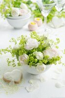 Arrangement of white roses and lady's mantle in china bowl next to heart-shaped, iced biscuit
