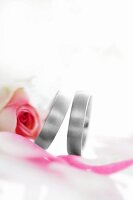 Two wedding rings with a pink rose