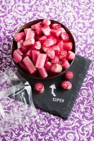 Bowl of red boiled sweets on slate board with stamped motif