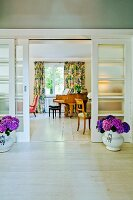 View into interior with sliding, glass 30s' doors flanked by vases of purple hydrangeas on pale wooden floor