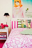 Large portrait of woman, scatter cushions with broad stripes and white and pink bed linen with large floral pattern in bedroom