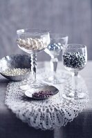Craft beads in silver dishes and wine glasses on lace doily