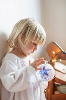 Little girl in nightshirt holding Christmas tree bauble