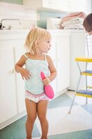 Little girl in underwear with hairbrush in kitchen with mother
