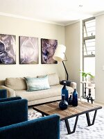 Corner of living room with organic photo prints above beige sofa and blue glass bottles on designer, wood and metal table