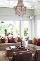 Sofa set with colourful scatter cushions around wicker coffee table and chandelier hanging amongst exposed roof structure in elegant living room