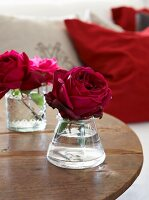 Romantic red roses in small glass vases on rustic wooden table