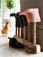 Wellington boots on vintage wooden rack; hen on veranda in background