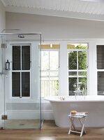 Modern, free-standing bathtub below window next to glazed shower area