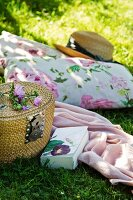 Floral cushions, straw hat, blanket, book and picnic basket on lawn