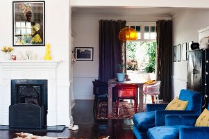 Blue velvet armchairs and colourful plexiglass furniture in dining area of interior with traditional fireplace