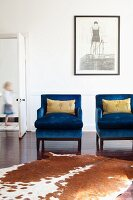 Animal-skin rug in front of bright blue armchairs and artwork on wall; door to one side