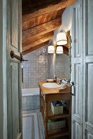 View into grey-tiled bathroom with rustic wooden washstand, mirror and sconce lamps