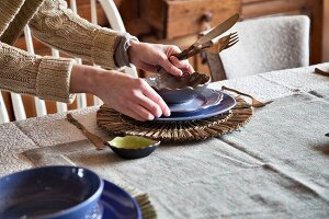 Woman setting table with cutlery, crockery & raffia placemat