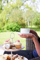 Woman sitting garden with cup of tea & pastries on cake stand