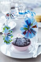 Muffin in pink paper case below glass cover decorated with paper rosettes