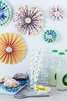 Colourful paper flowers decorating wall above party buffet with muffins