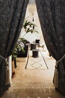 View through draped curtains to seating area with Oriental side tables and wool rug on highly decorative, brick-paved floor