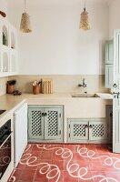 Oriental lattice doors below masonry kitchen counter; snaking, white pattern on tiled floor