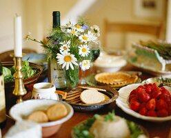 Schälchen mit Keksen und Erdbeeren, Margeritenstrauss und Kerzenständer auf einem Esstisch