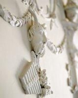 Dekorative Stuckarbeit an der Wand mit gehörntem Männerkopf über Weintrauben und Panflöte