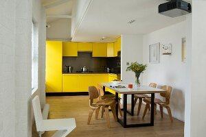 Einbauküche mit gelben Fronten und Designer Esstisch im offenen Grundriss eines Lofts