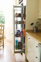 Einbauküche im Landhausstil mit Lenensmittelvorräten im hohen Schrankauszug