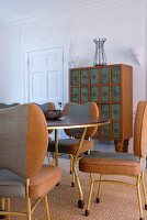Tubular steel chairs with grey and brown upholstery at dining table; postmodern chest of drawers in background