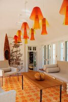 Interior with row of yellow and orange plexiglass pendant lamps and floor tiles in the same colours