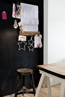 Vintage stool and old wooden table top on white trestles in front of black-painted pinboard with paper notes and stars