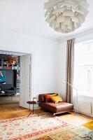 Patterned rug on parquet floor and brown leather armchair in corner between window and open double doors