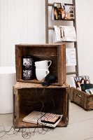 Vintage decor in old wooden crates in front of white-painted wood cladding and fashion magazines hung on rungs of ladder