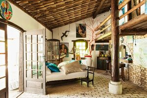 Bed between French windows in rustic bedroom with roof support and gallery structure; pictures of sea goddess Lemanja